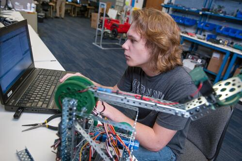 Male student in the Programming class works on programming some automation equipment