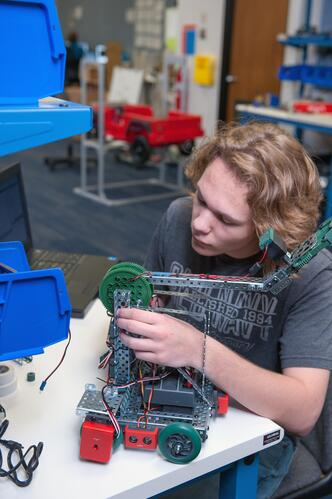 Male student in the programming class works on his automation equipment